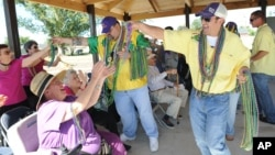 FILE - Seniors enjoy a Mardi Gras parade after they helped build a park in Houma, La. A new survey suggests pessimistic feelings held by people earlier in life take an optimistic turn as they move toward old age.