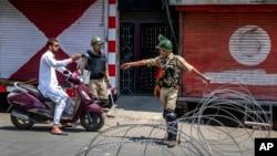 印度准军事士兵在铁丝网路检查站查问一名骑摩托车的人。(2017年7月7日)