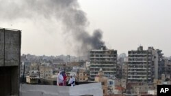 Smoke from burning tires rises over the Tripoli, Lebanon, skyline as people protest the killing Friday in Beirut of the country's intelligence chief, Brig. Gen. Wissam al-Hassan and at least seven others, October 20, 2012.