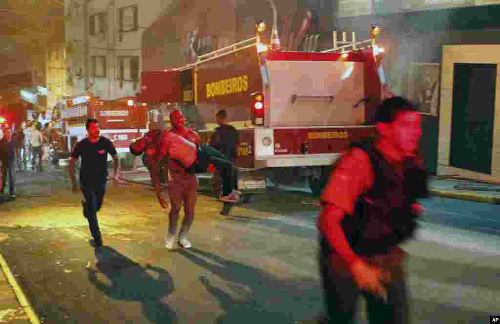 2013年1月27日一個人抬著在巴西聖瑪利亞城一家起火燃燒的夜總會裡受傷的人。