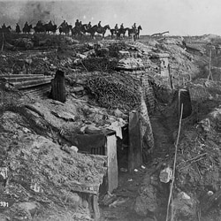 An abandoned British trench captured by the Germans. German soldiers are on horseback in the background.