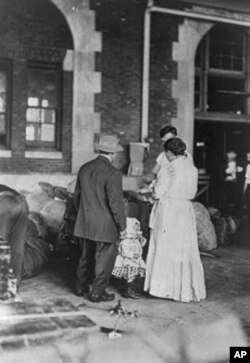 These immigrants gather around the family's belongings at the Ellis Island processing center. In the time it took them to pass inspection, they may have taken a new last name.