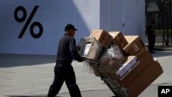 一名中国工人2019年4月4日用推车把货物送进北京一家商场。