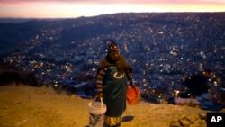 Une femme transportant deux seaux d'eau, La Paz, Bolivie, le 16 novembre 2016.