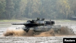 FILE - A Leopard 2 tank crosses a river during a German army, the Bundeswehr, training and information day in Munster, Germany, October 9, 2015.
