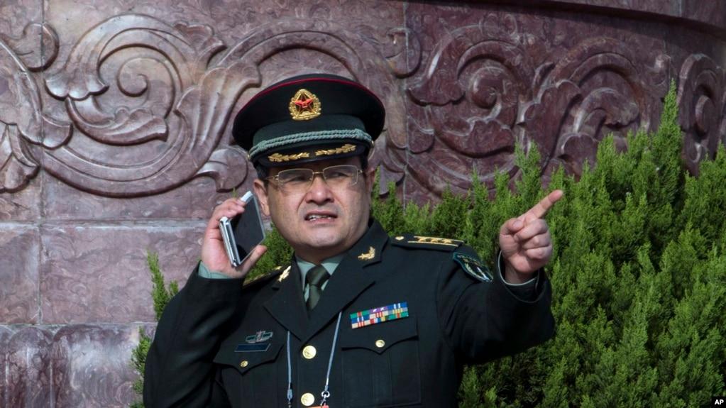 在北京人民大會堂外面,一位中國軍官使用手機(2015年3月4日)