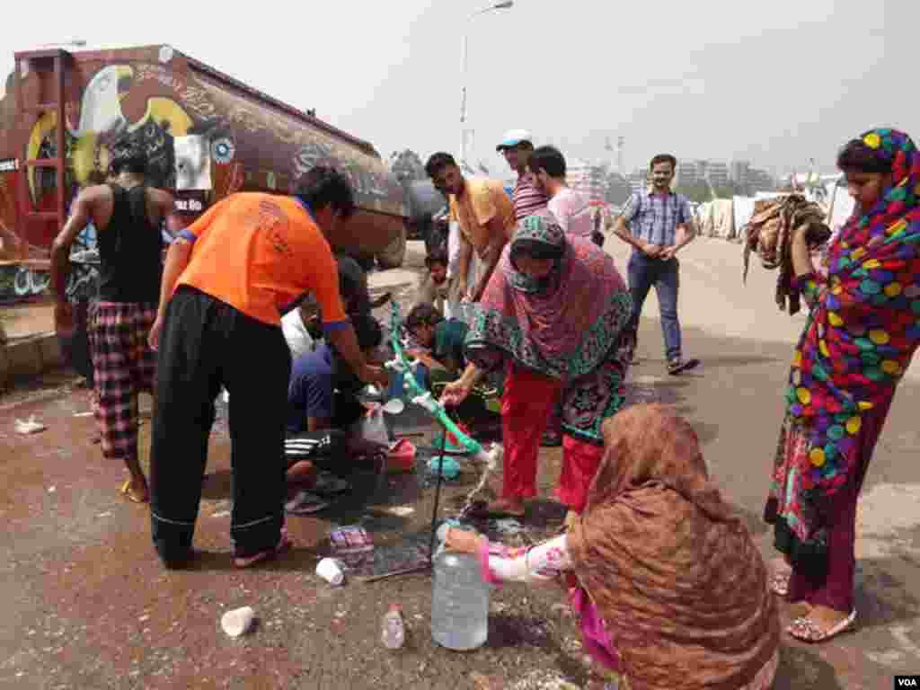 مظاہرین خیموں میں موجود کنٹینر سے پینے کا پانی بوتلوں میں بھر رہے ہیں