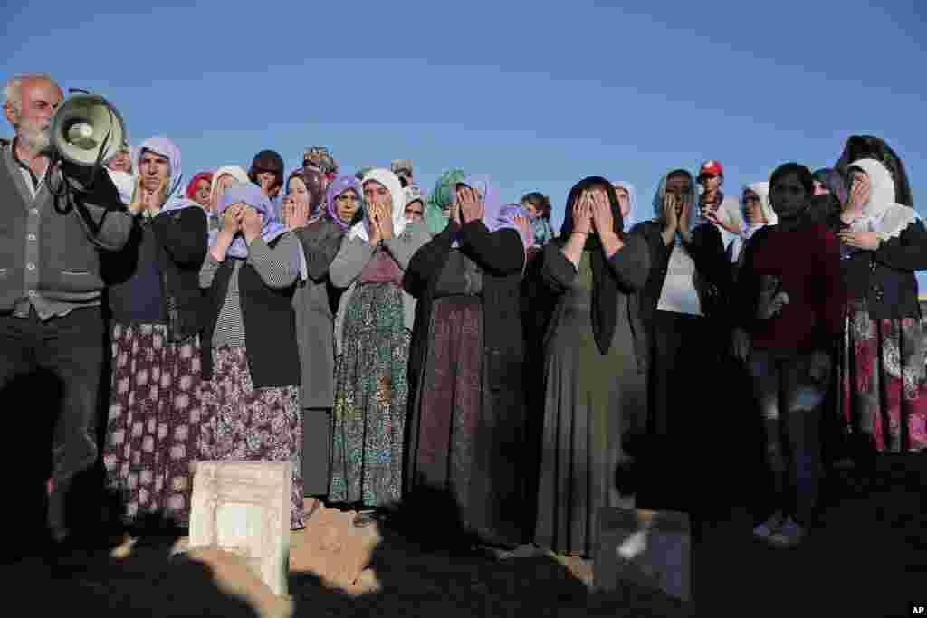 Kurdish mourners pray during the funeral of Kurdish fighters Hanim Dabaan, 20, Idris Ahmad, 30, and Mohammed Mustafa, 25, at a cemetery in Suruc, Turkey, Oct. 21, 2014.
