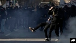 Protester kicks tear-gas canister toward riot police during minor clashes at a protest of the 24-hour strike in Athens, Feb. 20, 2013.
