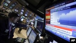 A television screen at the post of specialist Stephen Ruiz, left, displays the decision of the Federal Reserve, on the floor of the New York Stock Exchange Tuesday, Aug. 9, 2011.