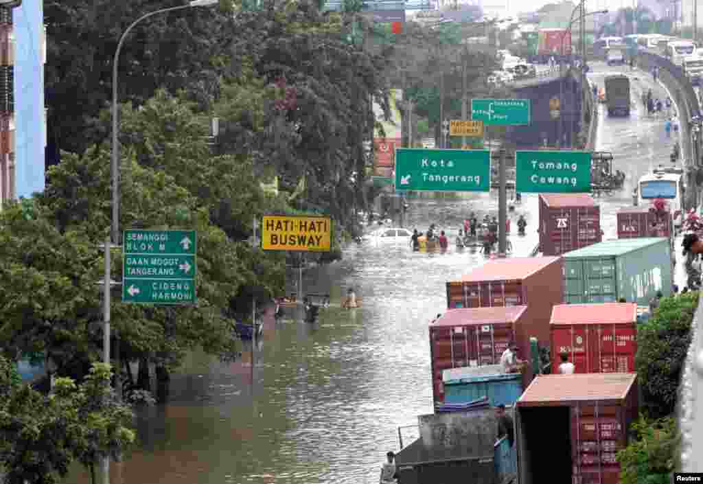 Container trucks are pictured stranded in flood waters on a road in west Jakarta January 18, 2013.