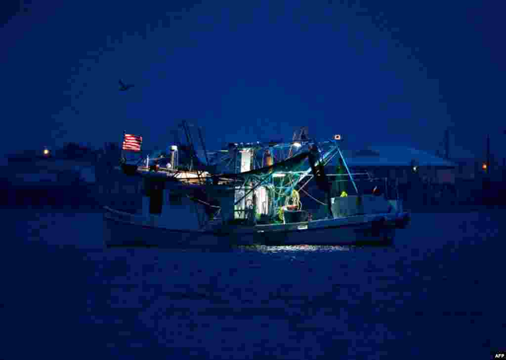 April 20: A commercial fishing boat sits anchored before sunrise in Grand Isle, La., a year after the Deepwater Horizon oil spill. (AP Photo/Patrick Semansky)
