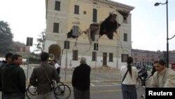 ປະຊາຊົນພາກັນອອກໄປຢືນຢູ່ກາງຖະໜົນ ຕໍ່ໜ້າຫ້ອງການເມືອງ Sant' Agostino ໃກ້ໆກັບເມືອງ Ferrara ຫລັງຈາກເກີດແຜ່ນດິນໄຫວ, ວັນທີ 20 ພືດສະພາ May 2012. REUTERS/Giorgio Benvenuti