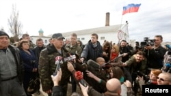 FILE - Colonel Sergei Storozhenko, commander of the military unit in the village of Perevalnoye, Crimea, talks to the media outside Simferopol, March 6, 2014, the day that Crimea's parliament voted to join Russia.