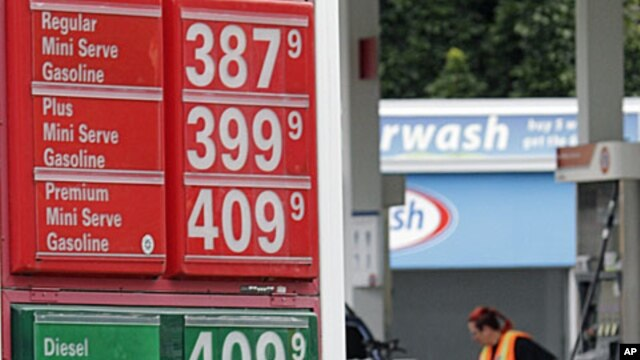 Prices are shown as Jaqueline Henderson pumps gas at a station in Portland, Ore., Friday, July 29, 2011
