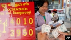 FILE - A currency trader counts Cambodian riels to exchange for U.S. dollars at a money exchange stall in the capital Phnom Penh, Cambodia, Feb. 15, 2008. Cambodia racked up $278 million in U.S. loans under the Lon Nol government in the 1970s.
