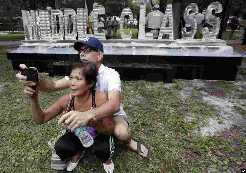 Poungsri and Scott se toman una foto frente a la escultura de hielo que se hizo durante las demostraciones en contra de la convención republicana en Tampa.