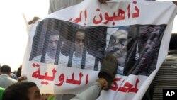 9月5日在开罗的法庭外,反穆巴拉克的抗议者用鞋拍击印有穆巴拉克头像的宣传品