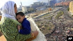 An Egyptian mother hugs her child as she watches thousands of Egyptian protesters gather at Tahrir square in Cairo, Egypt, Sunday, Jan. 30, 2011, with the ruling National Democratic party building burned at top right behind the red colored Egypt museum.