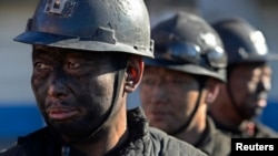 Miners wait in lines to shower during a break near a coal mine in Heshun county, Shanxi province, Dec. 5, 2014.