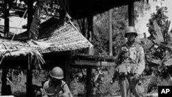 一名柬埔寨农民坐在一个骷髅旁,这是遭到红色高棉屠杀的平民的遗骨(资料照)