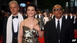 "Les acteurs William Shimell et Juliette Binoche avec le réalisateur Abbas Kiarostami arrivant pour la projection du film ""Copie Conforme"", au 63ème festival international du film, à Cannes, en France, le 18 mai 2010. (AP Photo/Lionel Cironneau)"