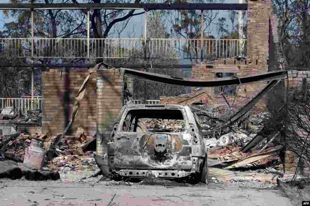 Chiếc xe bị cháy trơ khung trước của một ngôi nhà bị tàn phá bởi đám cháy rừng ở Winmalee, Australia. Cháy rừng hoành hành ở nhiều cộng đồng dân cư và phá hủy hàng trăm ngôi nhà ở đông nam Australia, hàng chục đám cháy vẫn ngoài tầm kiểm soát.