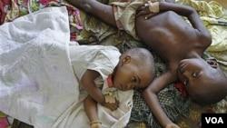 Dua orang anak Afrika yang menderita malaria dirawat di sebuah rumah sakit. Di Uganda utara, risiko tertular malaria paling tinggi di dunia.