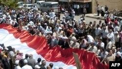 Pristalice sirijskog predsednika Bašara al-Asada nose ogromnu sirijsku zastavu na demonstracijama u selu al-Karja, najugozapadu Sirije