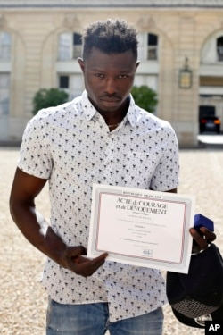 Mamoudou Gassama, 22, from Mali, displayed a certificate of courage and dedication signed by Paris Police Prefect Michel Delpuech as he leaves the presidential Elysee Palace after his meeting with French President Emmanuel Macron, in Paris, May, 28, 2018.