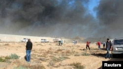 Black smoke billows from a warehouse after an airstrike in Zawura, west of Triploi, Libya, Dec. 2, 2014.