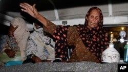 Seorang anggota keluarga perempuan hamil yang dilempari batu sampai matt di Lahore, Pakistan membawa jasadnya di ambulans pada hari Selasa, 27 Mei 2014. (Foto: dok.)