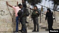 Cảnh sát biên giới Israel kiểm tra an ninh một thanh niên Palestine bên ngoài phố cổ Jerusalem trước buổi cầu nguyện ngày thứ Sáu 23/10/2015.