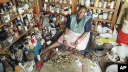 FILE - A witch doctor sits in her shop in South Africa, May 1994.