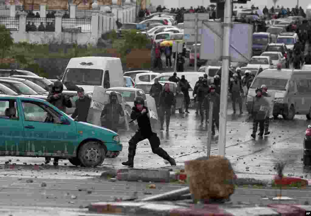 Riot police clash with protesters next to the cemetery where thousands of Tunisians gathered to attend the funeral of slain opposition leader Chokri Belaid, near Tunis, Feb. 8, 2013.