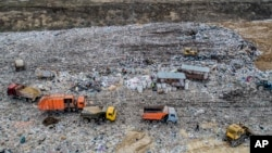 In this photo taken on Friday, April 20, 2018, garbage trucks unload the trash at the Volovichi landfill near Kolomna, Russia. Thousands of people are protesting the noxious fumes coming from overcrowded landfills surrounding Moscow.
