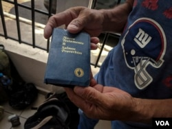 Mario Hernandez holds up a copy of the New Testament, one of the few items he carried with him on his journey north, from Chiquimulilla, Guatemala, to Mexicali, Mexico. (R. Taylor/VOA)