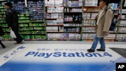 A shopper walks on the logo of Sony's PlayStation 4 at an electronics store in Tokyo, Dec. 25, 2014.