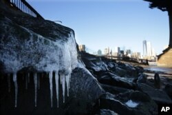 Ice forms on rocks on the Brooklyn waterfront across from lower Manhattan in New York, Jan. 7, 2014. The high temperature is expected to be 10 degrees in the city but wind chills will make it feel more like minus 10.