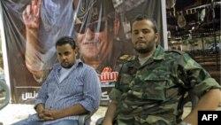 Ông Motasin Younis (trái), con trai và Mohammed Hamed Younis (phải) cháu của thủ lĩnh phiến quân Libya bị hạ sát, Tướng Abdel Fattah Younis, trong một cuộc phỏng vấn tại cứ địa của phe nổi dậy ở Benghazi, Libya, ngày 1 tháng 8, 2011