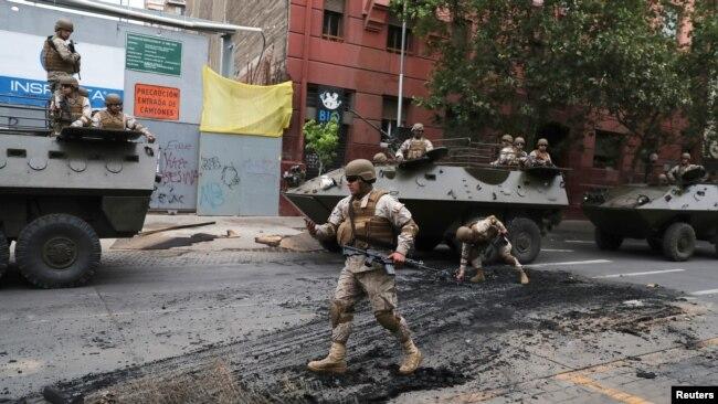 Soldados chilenos patrullan una calle de Santiago el domingo 20 de octubre de 2019, luego del toque de queda declarado por el gobierno el sábado por la noche. Reuters, Iván Alvarado.