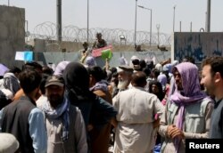 Crowds of people show their documents to U.S. troops outside the airport in Kabul, Afghanistan August 26, 2021. (REUTERS/Stringer)