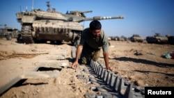6일 가자지구 국경 인근에서 이스라엘 군인이 탱크가 지나갈 수 있게 설치한 철로를 점검하고 있다. 이스라엘과 팔레스타인 무장정파 하마스는 7일 이집트 카이로에서 장기 휴전 협상을 계속했다.