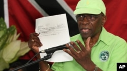 Former FIFA Vice President Jack Warner holds a copy of a check while he speaks at a political rally in Marabella, Trinidad and Tobago, June 3, 2015.