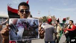 가다피 시신 사진을 들고 기뻐하는 한 남성