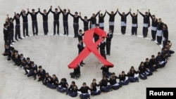 Students make a formation in the shape of a heart and a red ribbon during a HIV/AIDS awareness campaign.