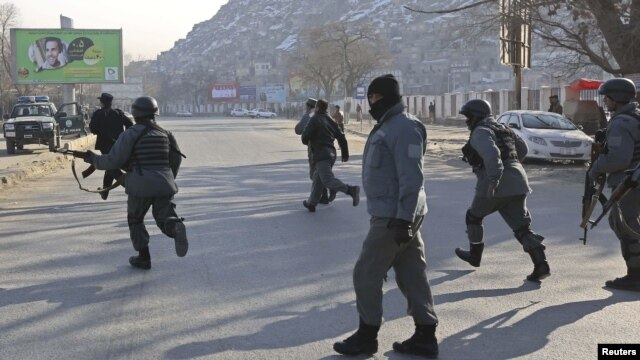 Afghan police officers run to the Kabul traffic police headquarters as it is attacked by insurgents in Kabul, January 21, 2013.