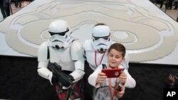 Penggemar berat Star Wars, Joseph Naiman, 7, berswafoto bersama orang tuanya Marshall (kiri), dan Danielle di sebelah peragaan figur mini LEGO Star Wars terbesar pada Perayaan Star Wars, 11 April 2019 di Chicago (foto: Alex Garcia/AP Images untuk the LEGO Group)