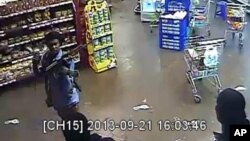 In this photo taken from footage from Citizen TV, via the Kenya Defense Forces and made available Friday, Oct. 4 2013, a man reported to be Omar Abdul Rahim Nabhan, one of the four armed militants walking in a store at the Westgate Mall.