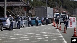 Police officers stop cars at a checkpoint near the town of Namie, Fukushima Prefecture, northeastern Japan, April 21, 2011